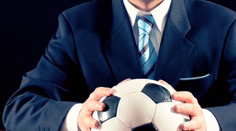 Человек держит футбольный мяч